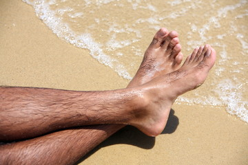 Man's bare feet on sand