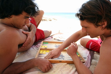 Two men on beach playing backgammon