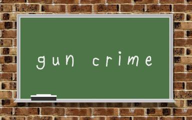 "Chalkboard with words ""gun crime"""