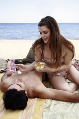 Female young adult feeding yogurt to male on beach