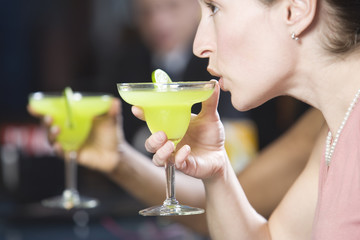 Side view of a young woman drinking a cocktail.