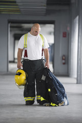 A Fireman holding a jacket and a hardhat.