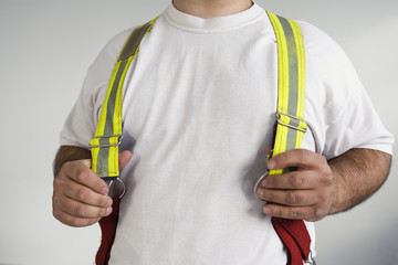 Midsection of a man wearing suspenders for a Fireman.