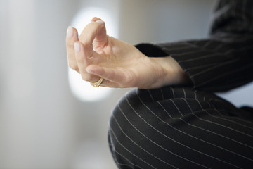 Close up of a woman's hand doing yoga.