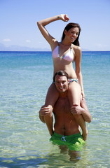 Young woman sitting on man's shoulders
