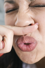Close up of a woman sneezing.
