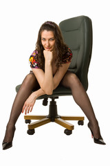Snazzy brunette sitting on the office chair in a very provocativ