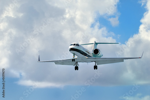 Private Corporate Business Jet close to landing. Blue cloudy sky