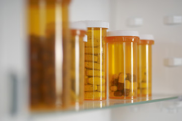 Bottles of pills in cabinet, close-up