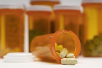 Bottles of pills, one spilling, close-up