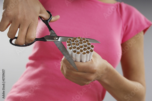 Woman cutting bundle of cigarettes, close-up