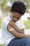 Boy 7-9 examining bandaid on arm, outdoors