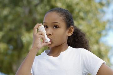Girl 7-9 using inhaler, outdoors