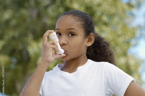 Girl 7-9 using inhaler, outdoors