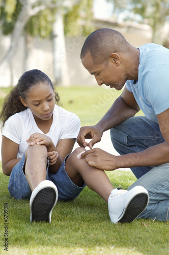 Father applying bandaid to daughter 7-9 in park