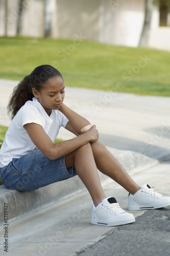 Girl 7-9 sitting on curb