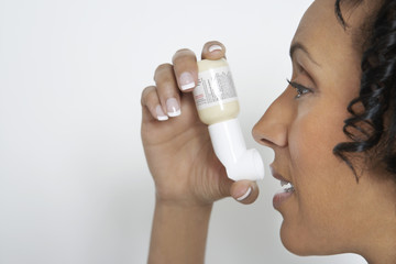 Woman using inhaler, studio shot