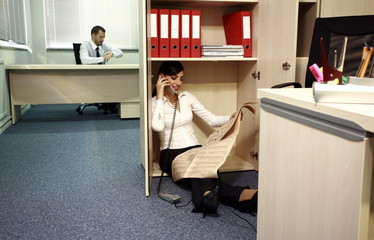 Office worker on the phone hiding from manager