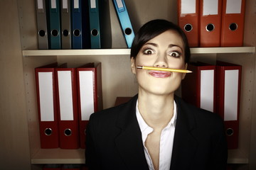 Office worker holding pencil with her upper lip