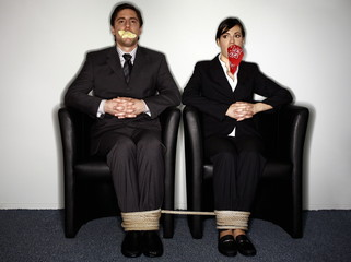 Male and female business people gagged and tied