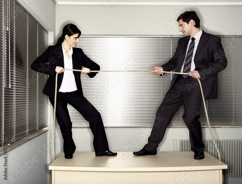 Male and female business people pulling ends of rope