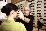 Optometrist adjusting glasses for woman in a store