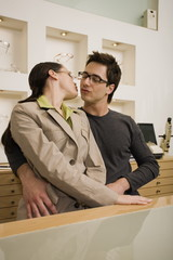 Couple about to kiss in eyeglasses store
