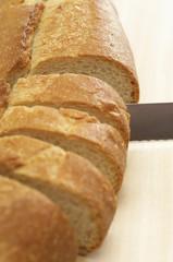 Close-up of knife slicing baguette