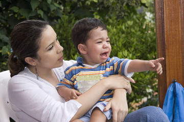 Little boy crying with his mother and pointing with his finger
