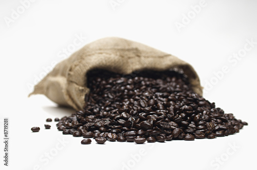 Coffee beans spilling from sack, close-up