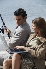Business couple on beach with fishing rod and laptop