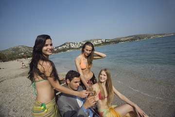 Businessman on beach with three women