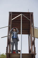 Businessman on life guard stand with binoculars