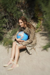 Businesswoman on beach with globe