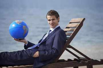 Businessman on chaise lounge with globe