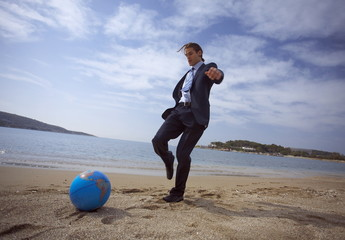 Businessman on beach with globe beach ball