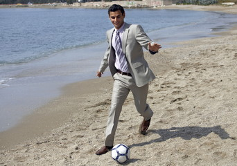 Businessman on beach playing soccer