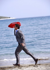 Businessman on beach with life preserver