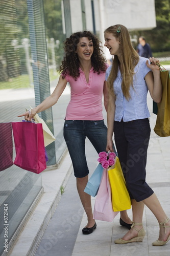 Two women with shopping bags looking at shop window