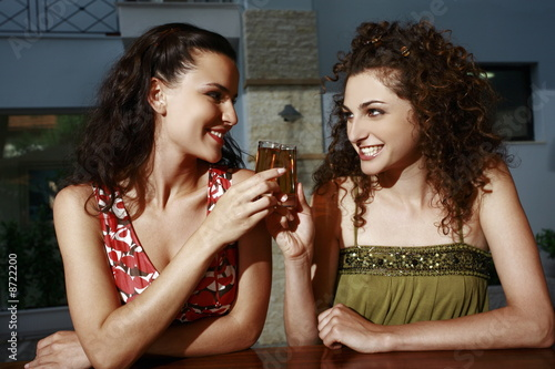 Two women in a bar toasting with shots
