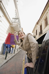 Woman leaning out of car with shopping bags
