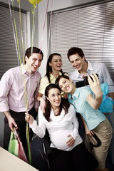 Office colleagues photographing at party with pregnant colleague