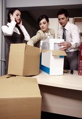 Three business people unpacking boxes in office