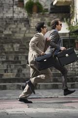 Two businessmen running