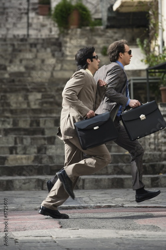 Two businessmen running