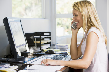 Woman in home office with computer using telephone smiling