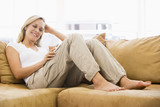 Fototapety Woman in living room listening to MP3 player smiling