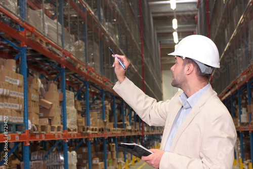 worker counting stocks in warehouse - 8729470