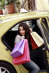 Woman with shopping bags getting out of a taxi