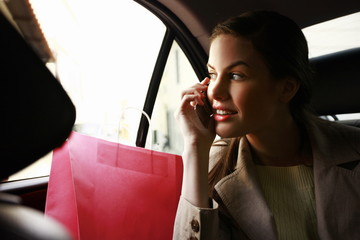 Woman on the cell phone with shopping bags in a taxi